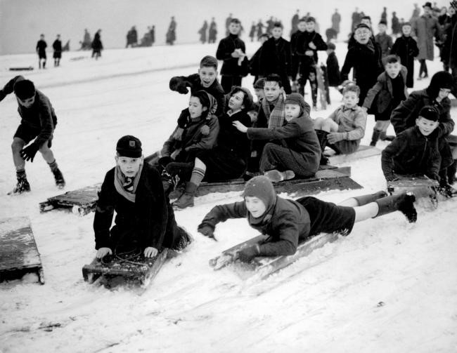 Note the balaclavas, short trousers, wellies and homemade sledges – children were fearless then!